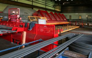 A steel worker operates a big red machine