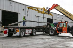 Steel workers unloading metal rods from a truck