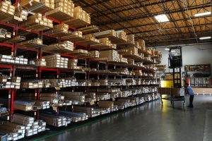 A forklift unloads from the FRY warehouse shelves, full of different boxes.