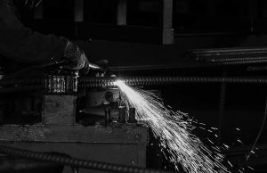 Black and white photo of steel sparks flying around
