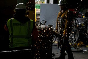 Steel sparks float in air near some workers