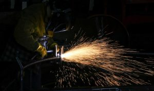 Sparks fly as a Steel Worker cuts through metal