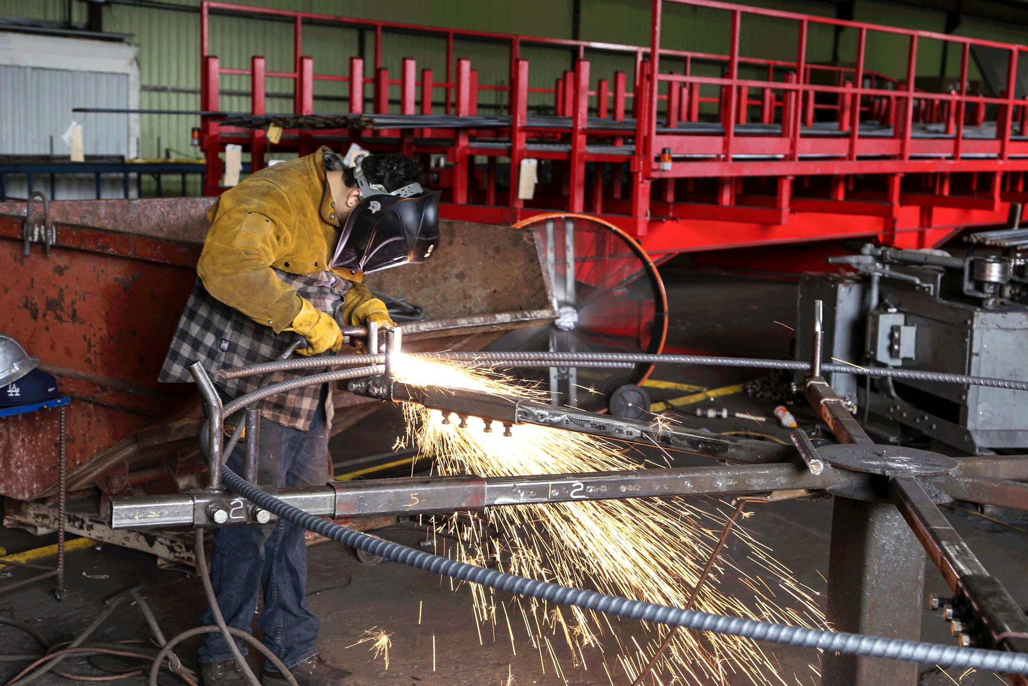 Sparks flying while a work cuts through steel.