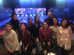People posing in the bowling alley by the lanes.
