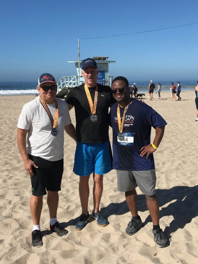 Three people standing on the beach with triathlon medals.